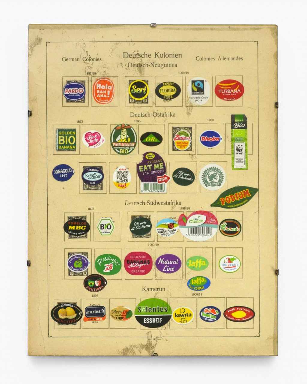 """""""Deutsche Kolonien"""" – """"German colonies"""", 2016, fruit stickers from all over the world on the pages of a historical album for stamps of German colonies, clip frame 31 x 23 cm"""